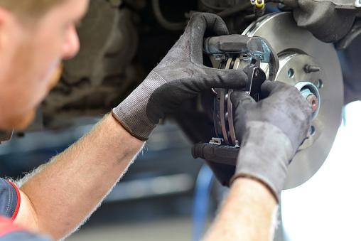 car mechanic repairs breakes from vehicle in a workshop
